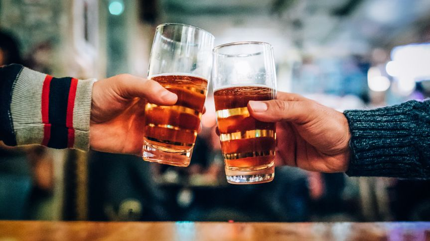 friends cheersing at bar with beer