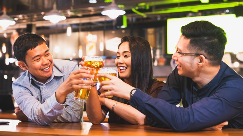 Group of happy Asian friend or office colleague coworker celebrate toast beer pint together at pub restaurant or night club.