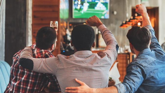 Three men watching football on TV in sport bar, back view.