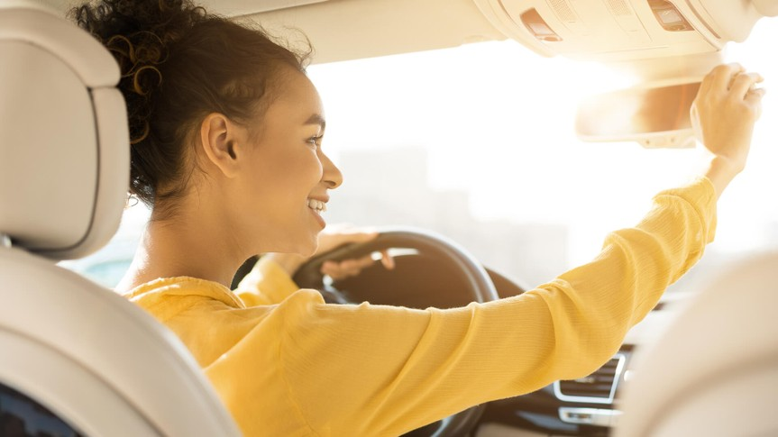 Happy black girl touching rear view mirror, driving car and smiling, copy space.