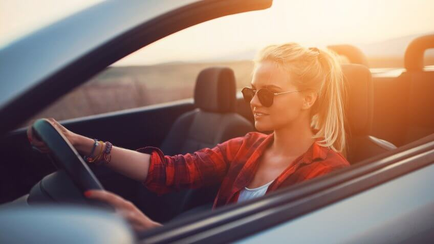 Beautiful young woman with sunglasses driving a cabrio.