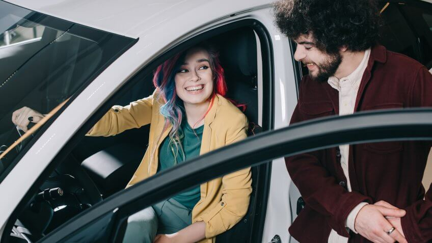 overhead view of cheerful girl with colored hair sitting in car and looking at curly man.