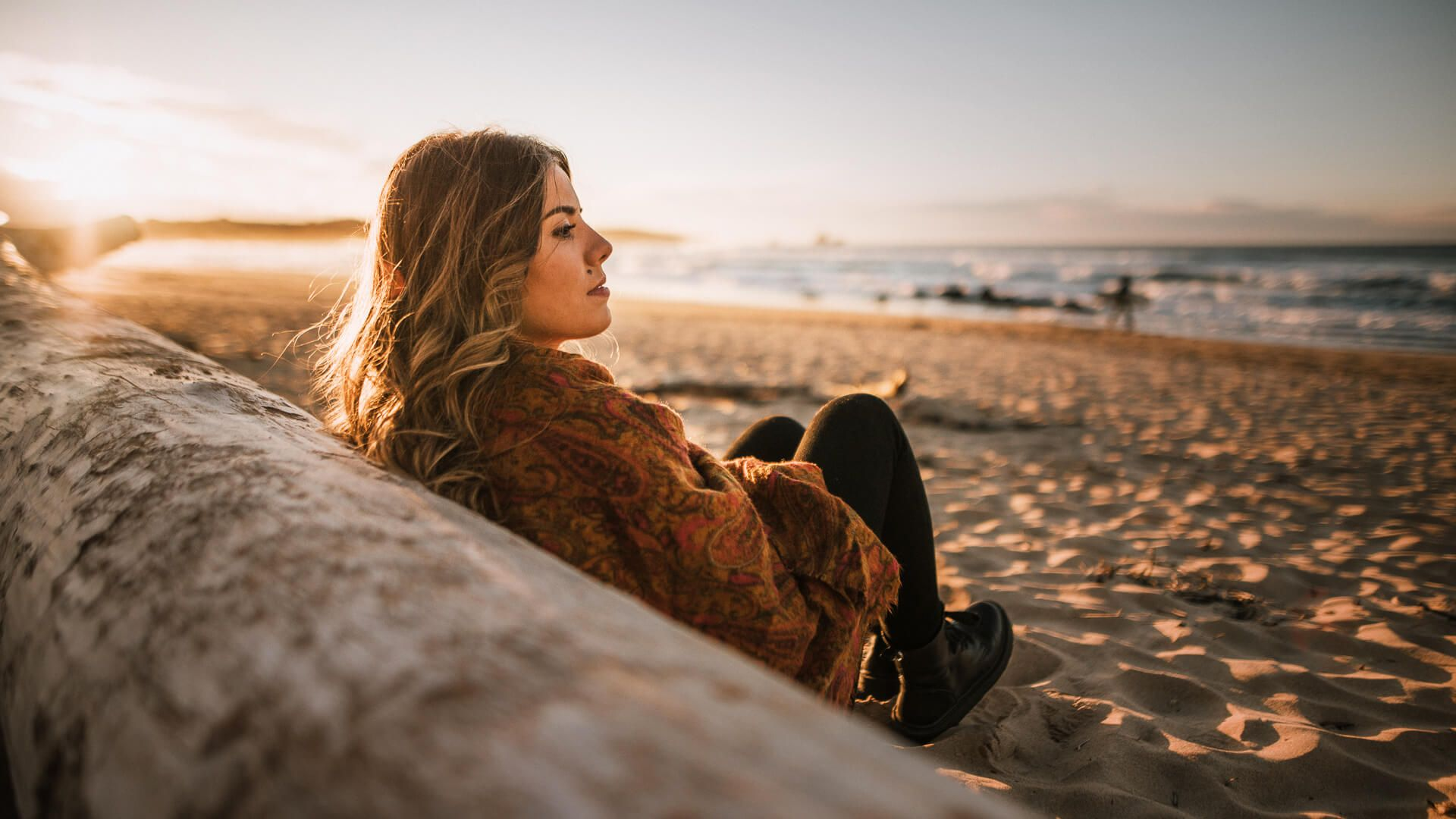 Young woman sitting by a beach at sunset in winter.