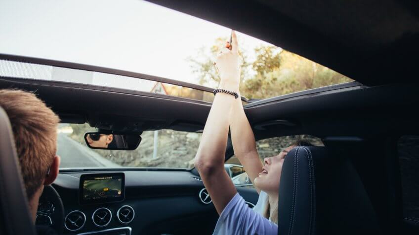 girl taking photo out of sun roof in car