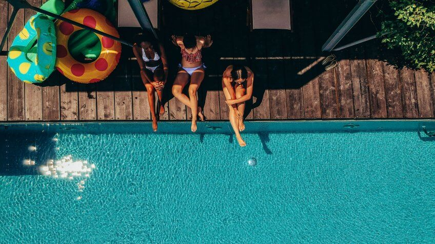 Aerial view of a three friends relaxing by the pool.