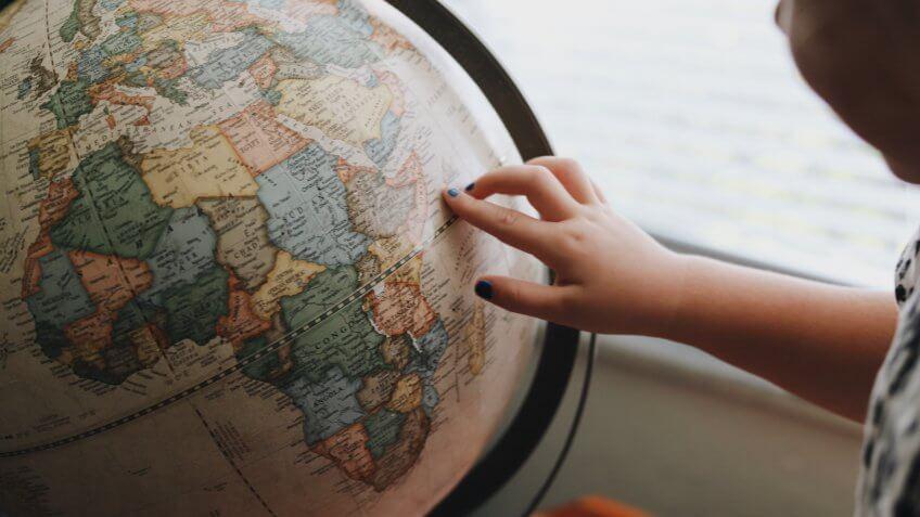child pointing finger at globe