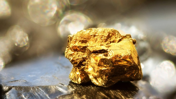 Golden bar on raw coal nuggets with soft focus and shiny background.
