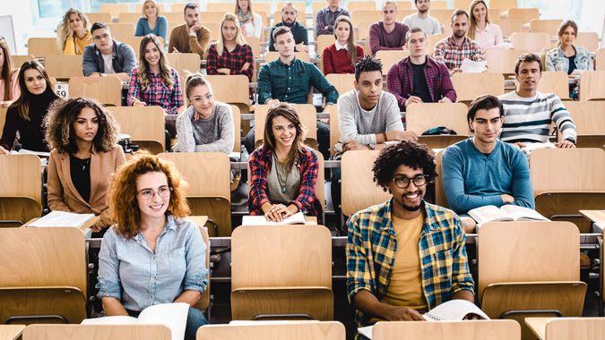 Large group of happy college students attending a class in amphitheater.