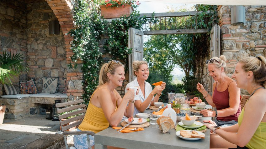 Small group of women are having breakfast together in their holiday villa courtyard in Tuscany.