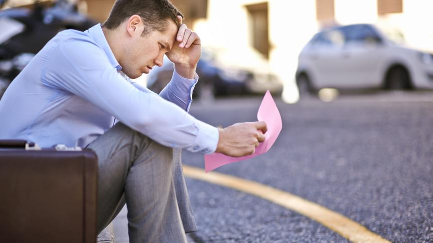 A businessman holding a pink slip terminating his employmenthttp://195.