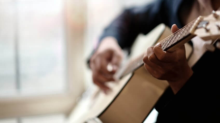 Cropped shot of man practicing in playing acoustic guitar.
