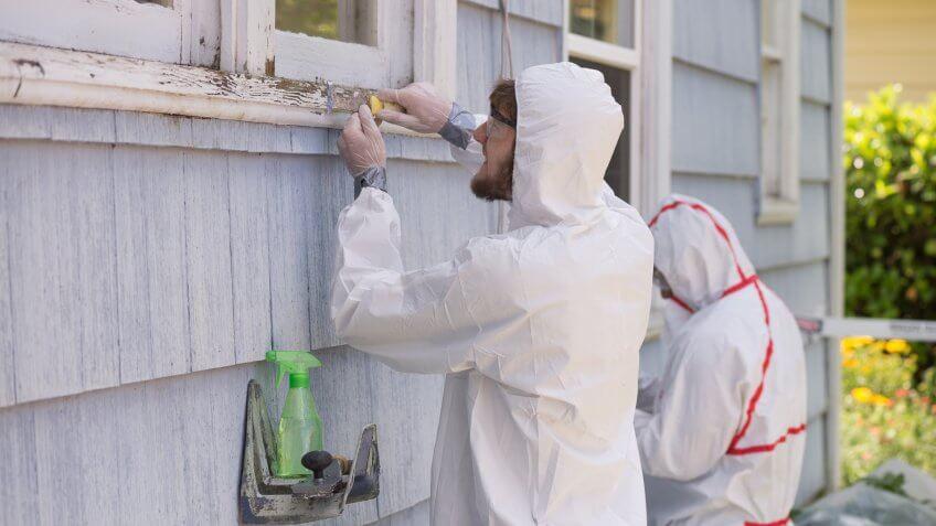 hazmat suit workers scrape off paint