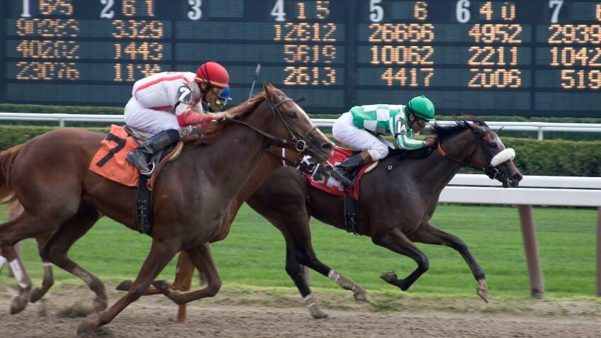 horse jockeys racing horses