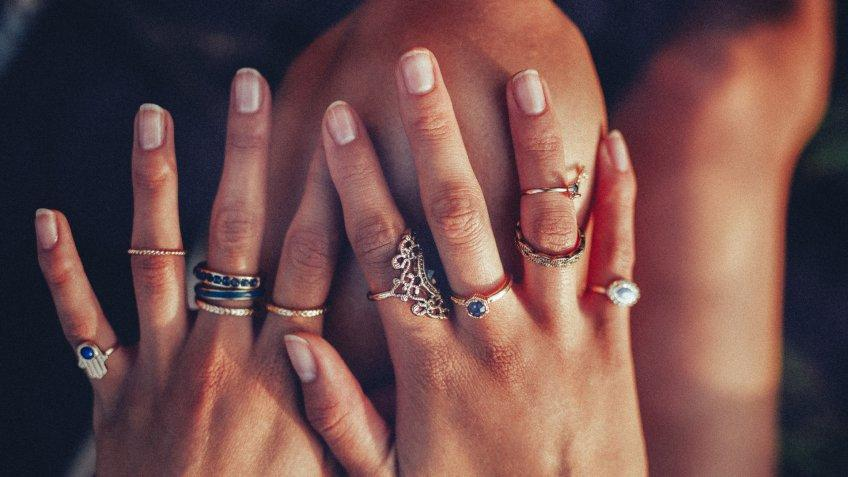 Cropped closeup of a boho girl's hands with many rings on her fingers, in gold and silver with dark blue stones.