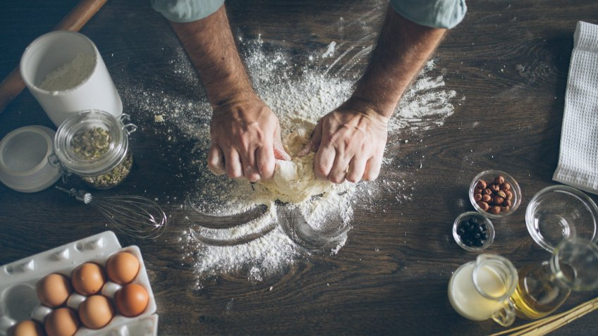 Pastry chef kneading dough in kitchen.