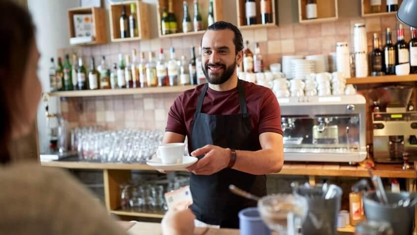male barista serving coffee