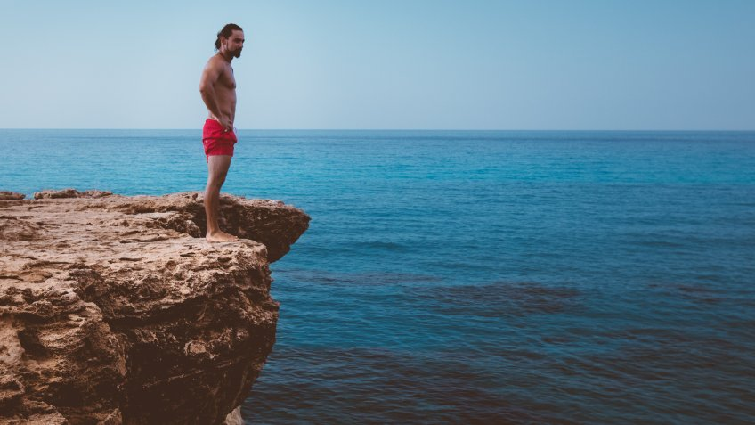 Young active diver standing on cliff looking at sea and preparing to dive into ocean.
