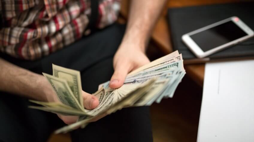 man counting usa dollars, focus on banknotes.