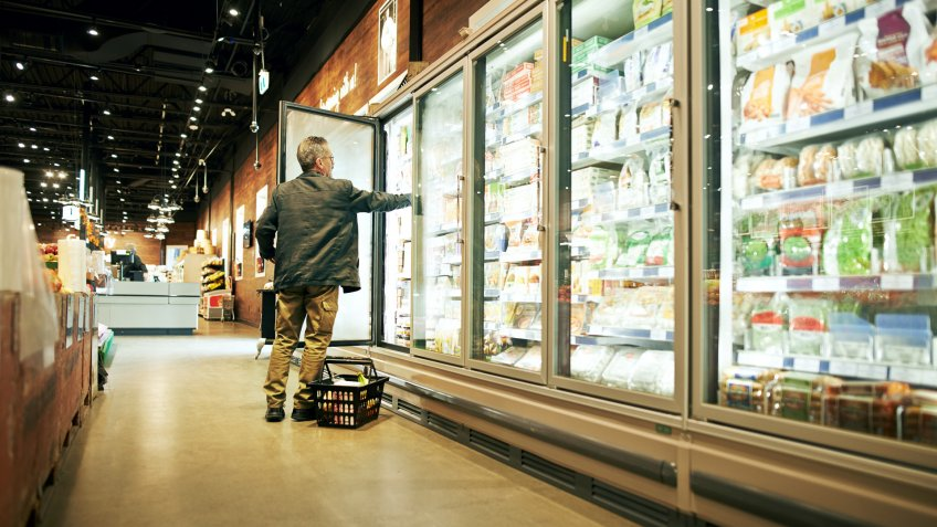 Shot of a mature man shopping in the cold produce section of a supermarket.
