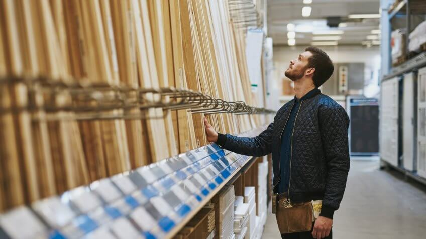 man in hardware shop looking for wood