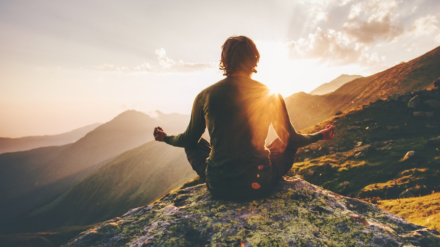 Man meditating yoga at sunset mountains Travel Lifestyle relaxation emotional concept adventure summer vacations outdoor harmony with nature.