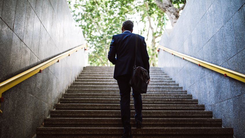 Pedestrian Businessman Walking Out Of Metro Up Stairs On Sunny Morning.