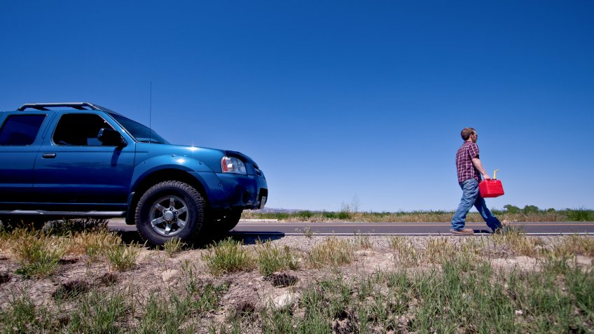Young man filling empty gas tank in his pickup with a gas can.