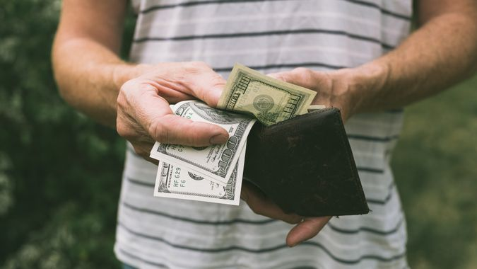 An unidentifiable man holding some one hundred dollar bills, that he has picked out of an old worn brown wallet.