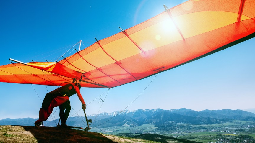 Man with hang-glider starting to fly from the hill top.