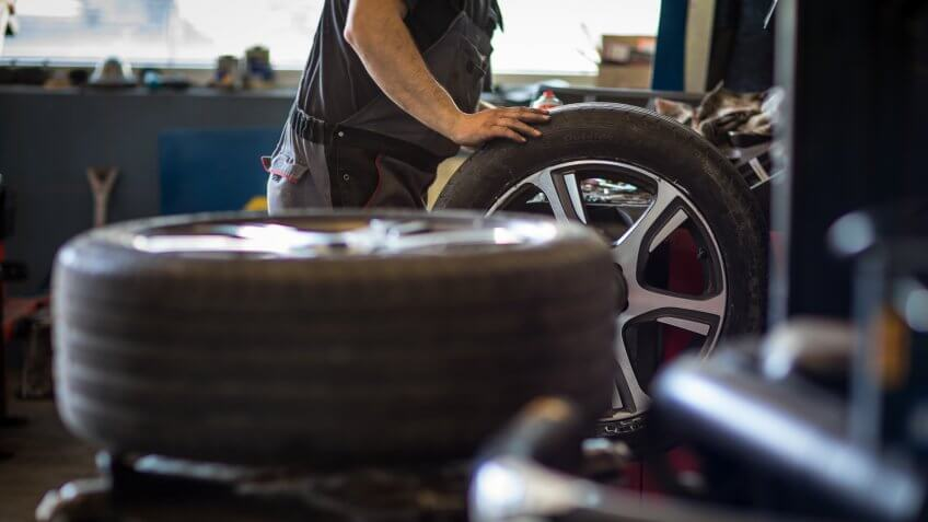 Wheel balancing or repair and change car tire at auto service garage or workshop by mechanic.