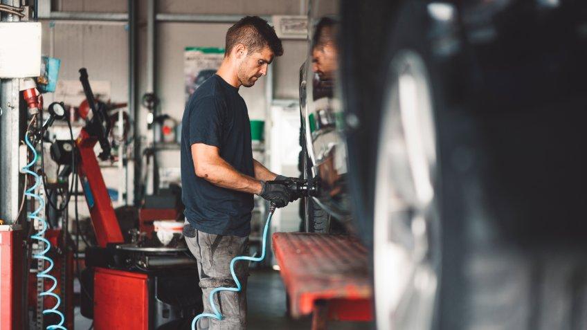 Vulcaniser work-shop, changing tires on a car.