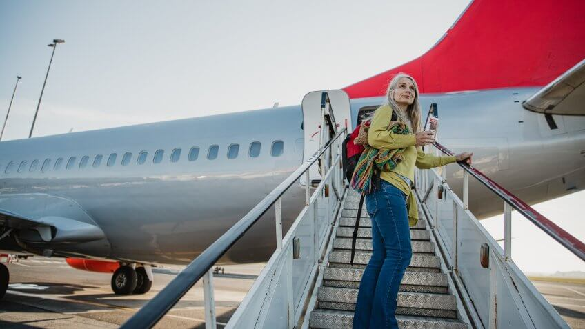 One mature woman is standing on the air-stair of her plane with her boarding pass and has turned round to give one last look to her home before she goes travelling.