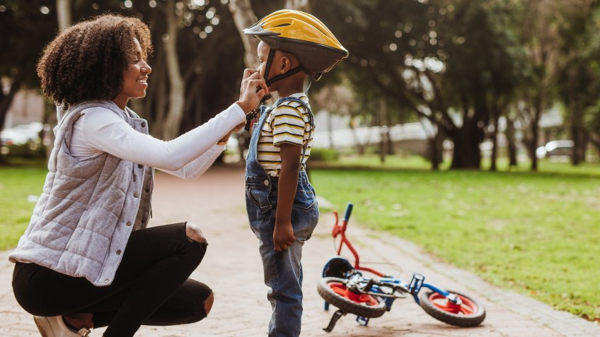 Mother helping son wearing helmet for cycling at park.