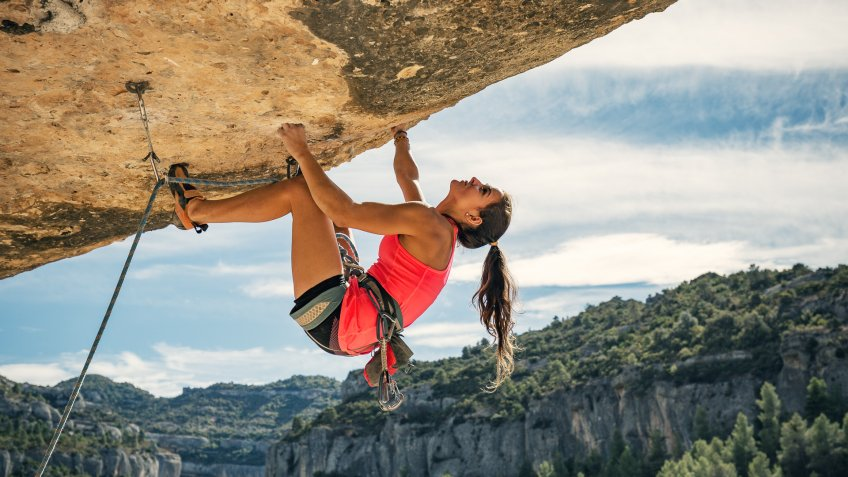 Young woman rock climbing in Margalef Catalonia Spain.