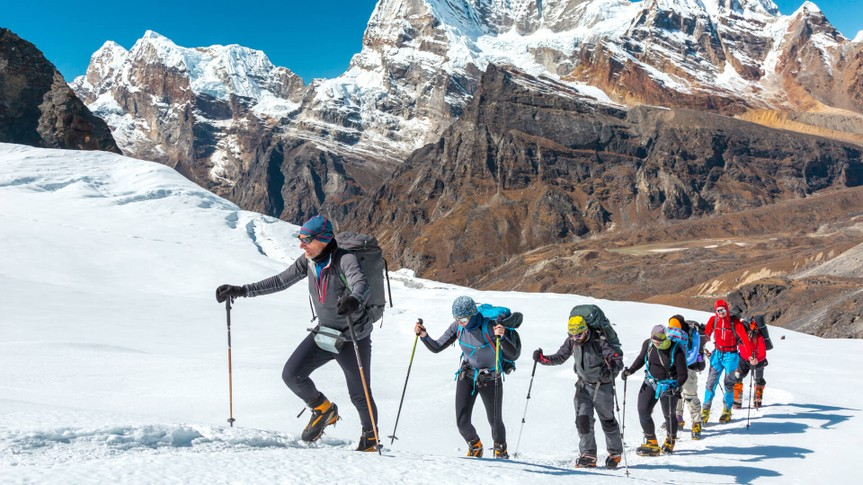 Adventurous People of variety of Age Origin and Ethnicity making Climb in high Altitude Mountains walking on Glacier with heavy Snow using trekking Poles and other Gear.