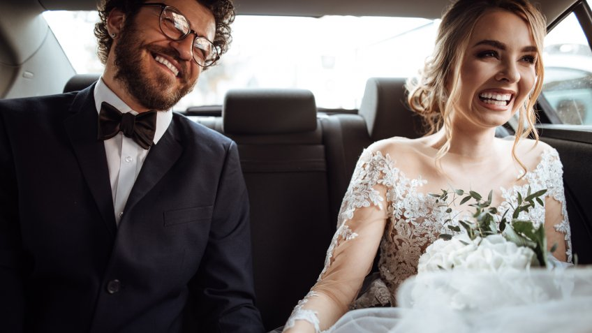 Newlyweds holding hands in the backseat.