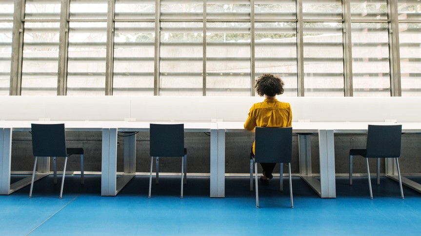 Rear view of young student or businesswoman sitting on desk in room in a library or office.