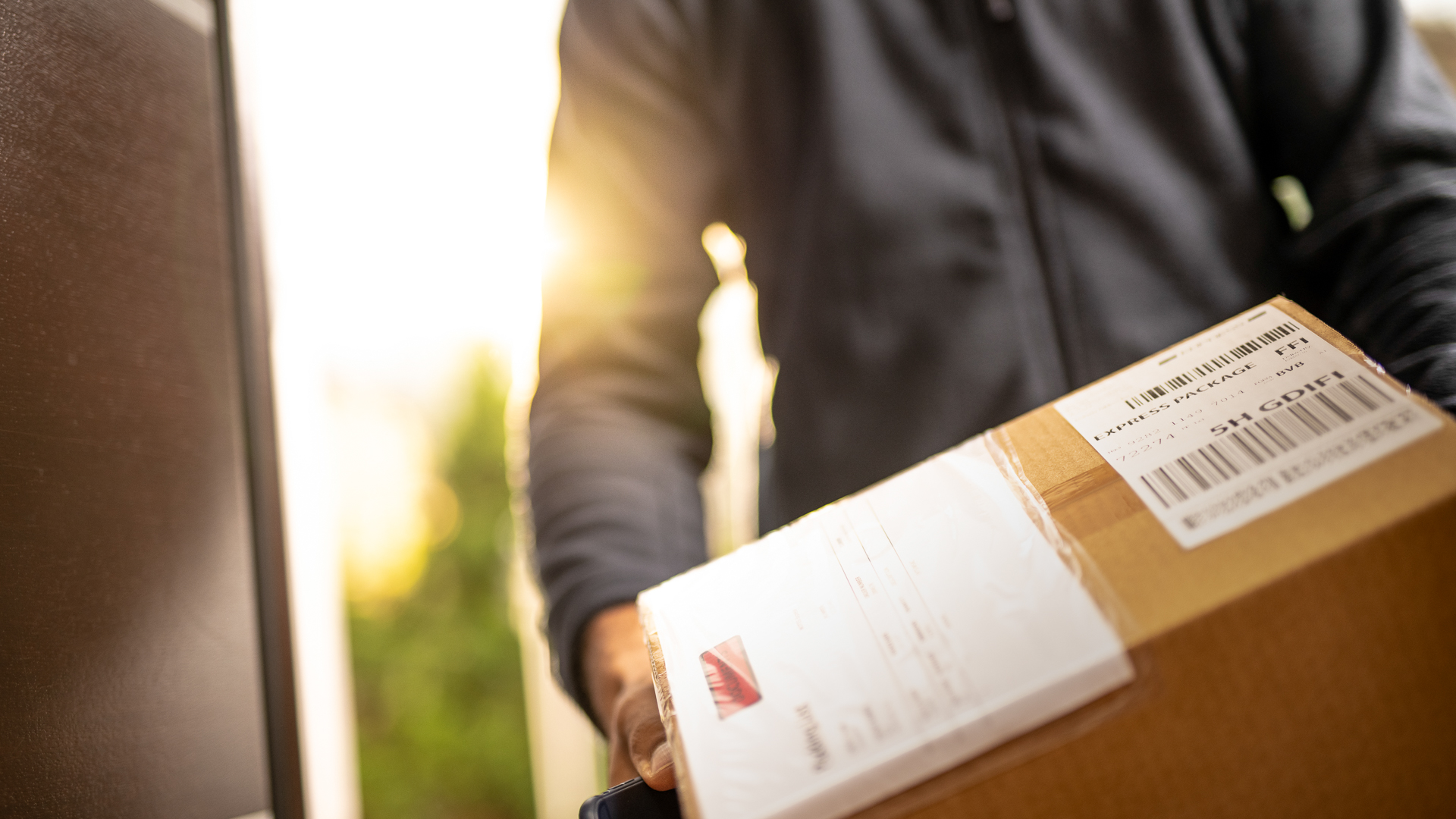 Close up of an unrecognisable courier holding cardboard box prepared for home delivery.
