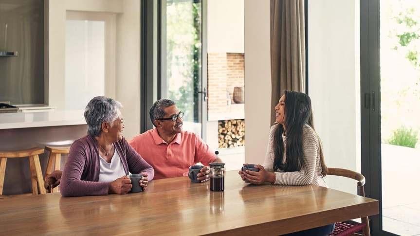 Shot of a young woman chatting and having coffee with her parents at home.