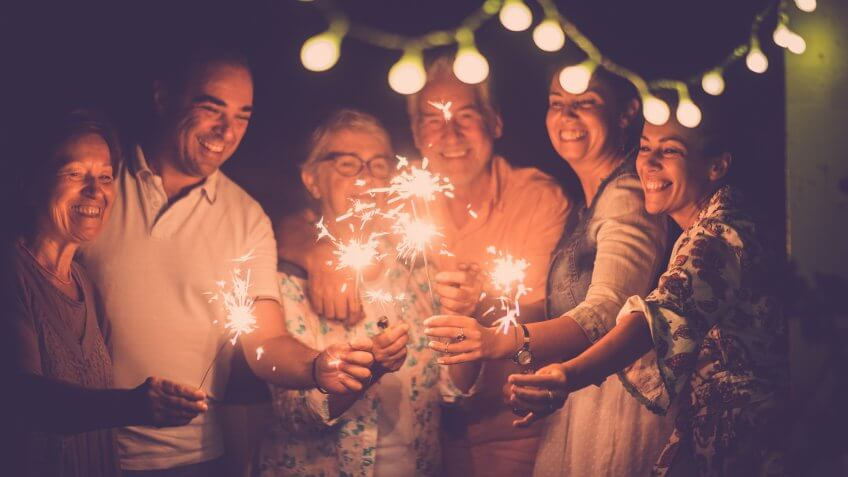 group of caucasian people friends with different ages celebrate together a birthday or new year eve by night outdoor at home.