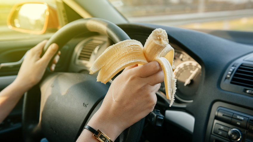 person eating banana snack in car
