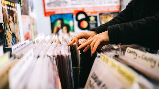 An unrecognisable male customer searches through and selects a second hand vinyl record from a shelf in a record store, hands only, horizontal composition.