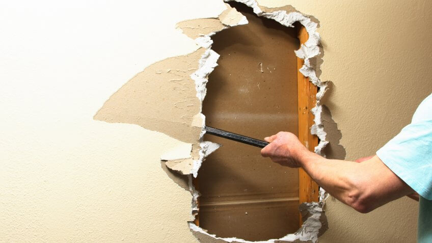 Handyman removing sheetrock from a wall with a pry bar.