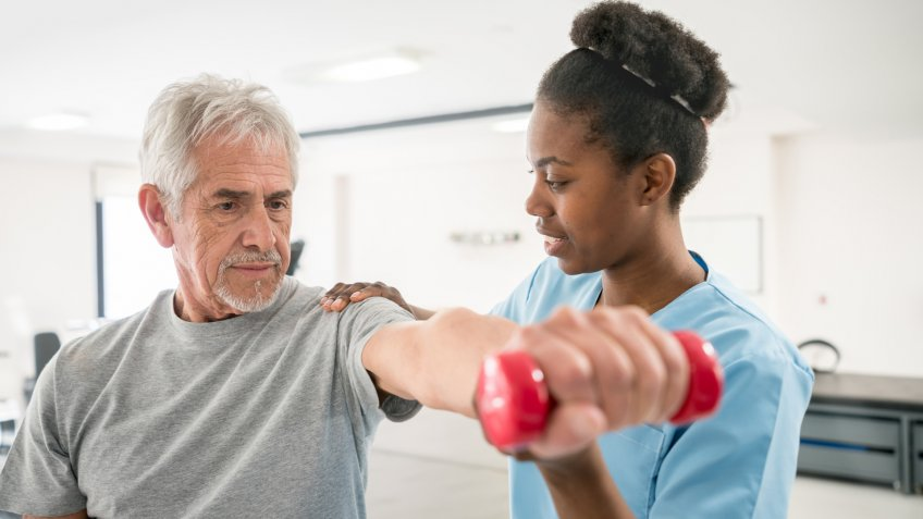 Physiotherapist correcting her senior patient with his shoulder posture as he lifts free weights both looking focused and smiling.