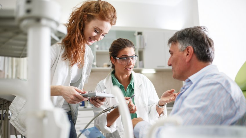 physicians assistant with doctor and patient