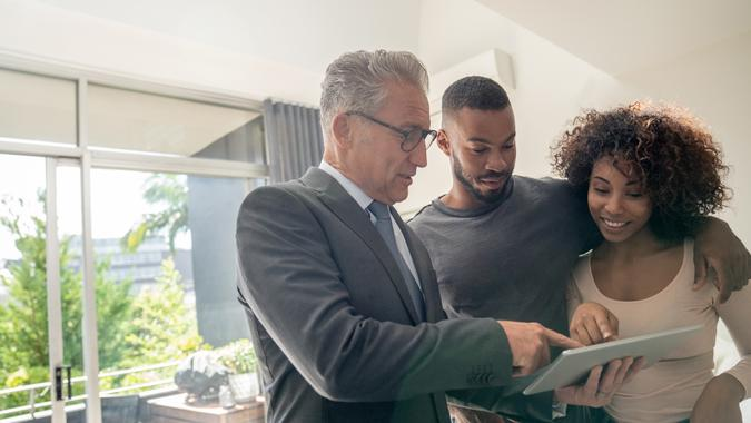 Real estate agent showing a property to a happy African American couple using a tablet computer – lifestyle concepts.