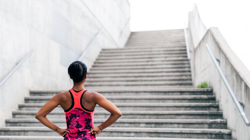 Young woman standing in front of a set of stairs, preparation and determination.