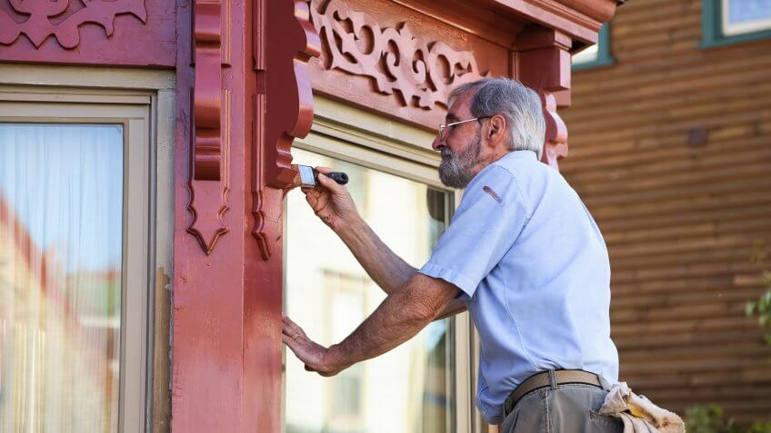 An older man in an historic town paints his house, with careful attention to detail, while standing on a ladder.