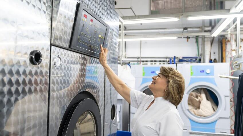 Mature woman working at a laundry service operating an industrial washing machine smiling very happy.