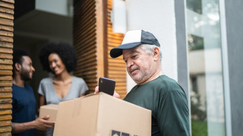 Courier delivering boxes to a young couple.